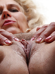 Curly-haired GILF showing off her wrinkly pussy up close and personal