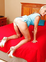 Short-haired blonde GILF gleefully masturbating on a big red bed